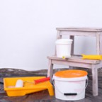 Buckets with paint and ladder on wall background. Conceptual pho